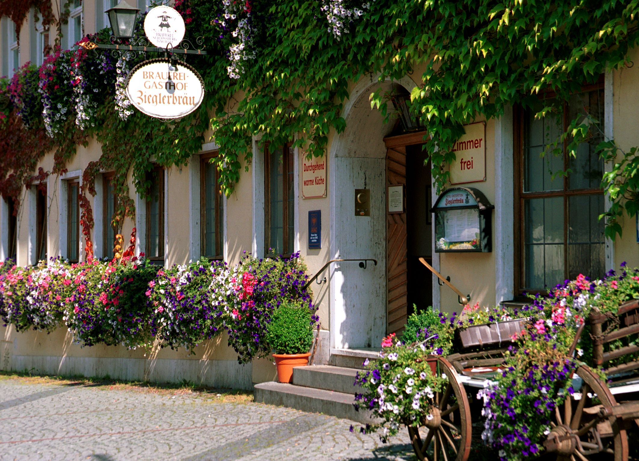 Photo of exterior view of Altstadthotel Zieglerbräu with blooming flower boxes and entrance door, photo: Altstadthotel Zieglerbräu