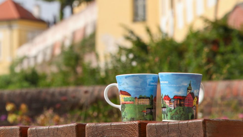 Photos of cups with colourful art print in front of the castle wall, Dachau Castle