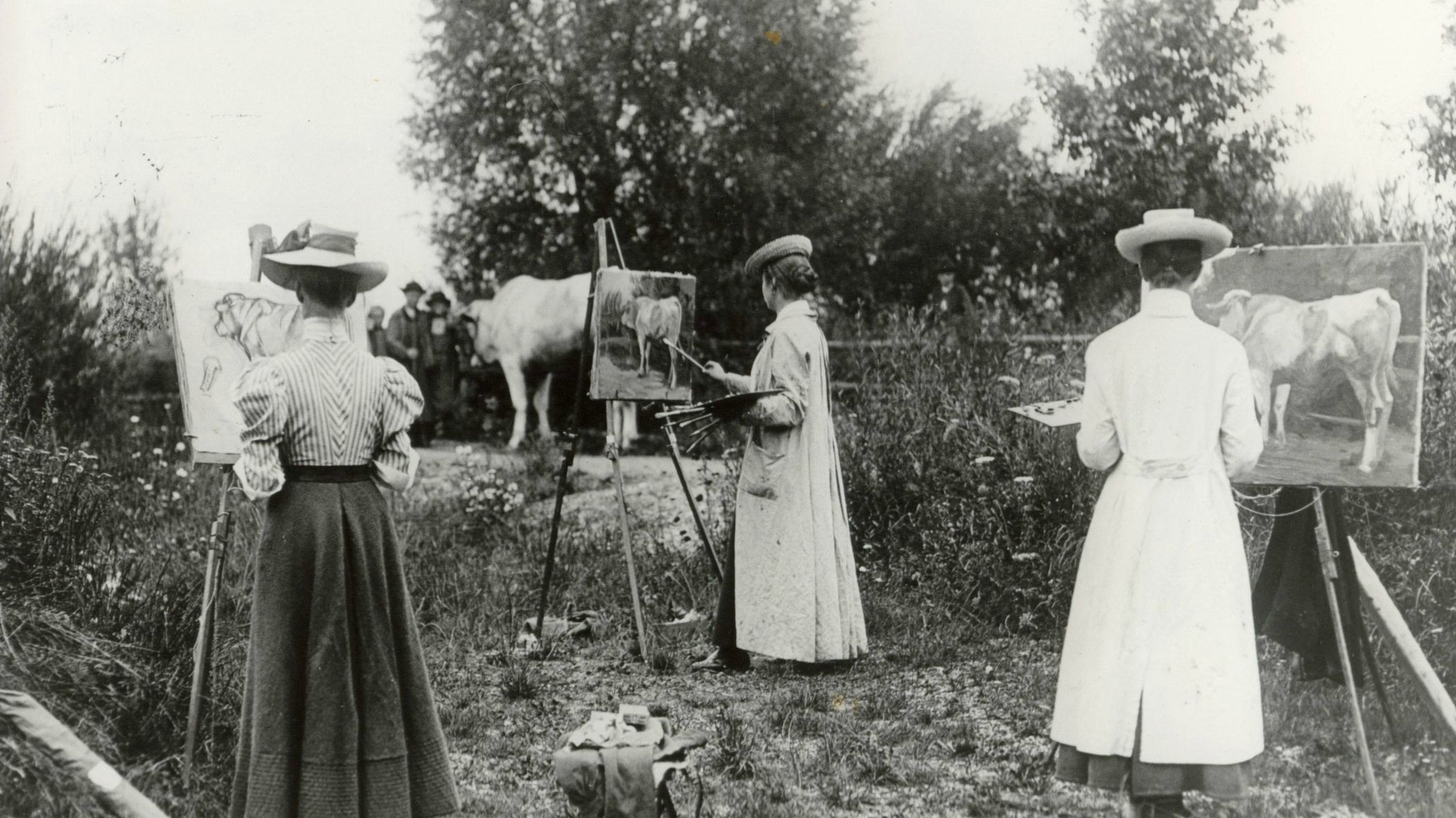 Black and white photographie of a womens' outdoor painting class around the year 1900 with easels and cow, trees in the background. Photo: Zweckverband Dachauer Galerien und Museen.